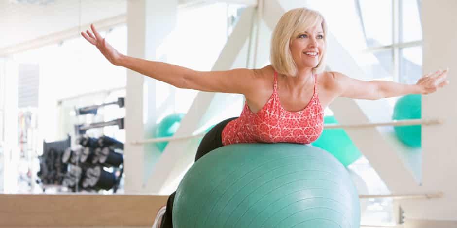 Kvinne strekker nakke og skulderblader på terapiball