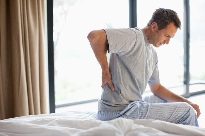 Stiv rygg om morningen i sengen