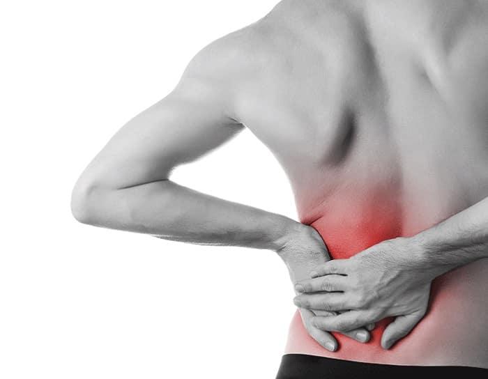 Mann holder seg til venstre del av korsryggen med smerter