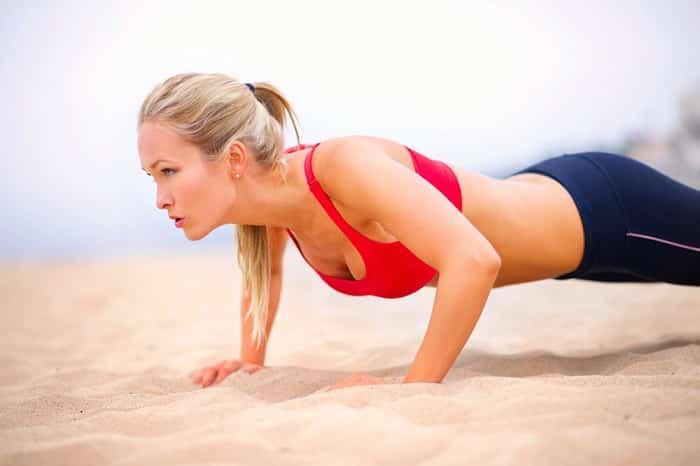 kvinne som trener i sand 700